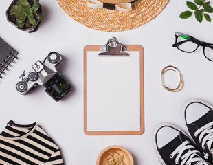 Stylish feminine accessories and clipboard with blank paper
