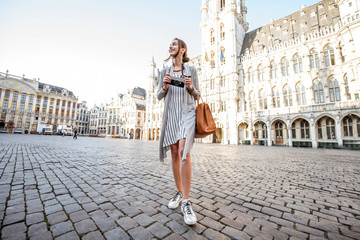 Tuinposter Brussel Young female tourist walking on the main square with city hall in the old town of Brussels in Belgium
