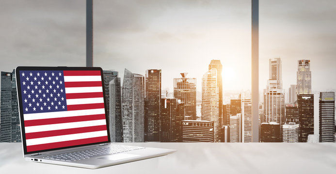 Independence Day on office laptop screen with panoramic sunset view of modern downtown skyscrapers at business district