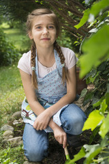 Portrait of girl with pigtails gardening