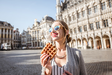 Young woman walking with waffle a traditional belgian pastry food in the center of Brussels city during the morning