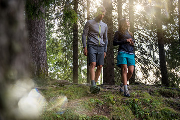 Man and woman couple walking in forest woods with sun flare light. Group of friends people summer adventure journey in mountain nature outdoors. Travel exploring Alps, Dolomites, Italy.