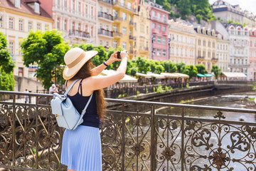 Woman taking pictures with smartphone. Stylish summer traveler woman in hat with camera outdoors in european city, old town Karlovy Vary in the background, Czech Republic, Europe