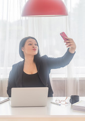 Selfie time.Elegant young business woman taking selfie at office