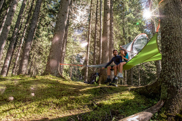 happy woman man couple relaxing in hanging tent camping in forest woods during sunny day.Group of friends people summer adventure journey in mountain nature outdoors.Travel exploring Alps,Dolomites