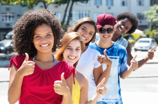 Lachende Jugendliche in einer Reihe zeigen Daumen