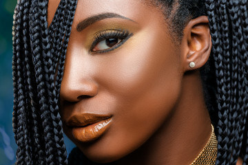 Macro beauty face shot of african girl with braids.