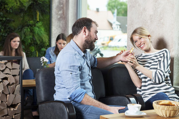 Couple flirting in a cafe, people in background