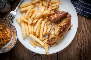 Roasted chicken with french fries on a plate.