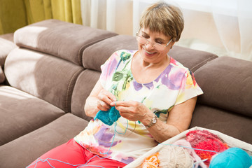 An elderly woman is knitting sitting on a sofa in the room