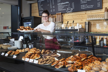 Waitress in coffee shop arranging croissants on counter