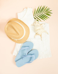 Summer fashion, summer outfit on cream background. White lace dress, blue flip flops, seashell and straw hat. Flat lay, top view