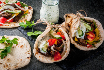 Spoed Fotobehang Voorgerecht Healthy snack, lunch. Traditional Greek wrapped sandwich gyros - tortillas, bread pita with a filling of vegetables, beef meat and sauce tzatziki. On black stone table Copy space