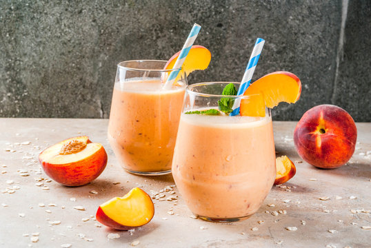 Healthy eating. Breakfast, snack. Drink smoothies from fresh peach, milk (yogurt) and oatmeal, decorated with mint leaves, with striped straws. On a light stone table. Copy space