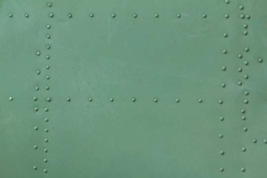 Old painted metal background detail of a military aircraft, surface corrosion.