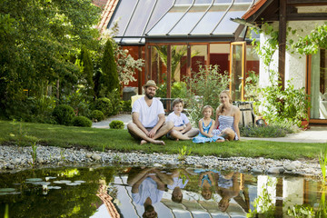 Family with two children takes a break by the pond, Munich, Bavaria, Germany