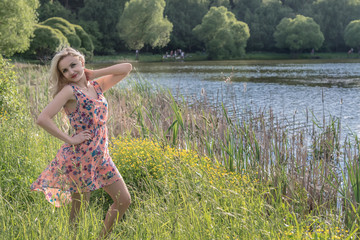 A young fair-haired girl is standing on the picturesque shore of the pond on a summer day