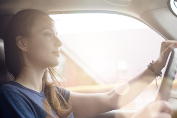 The beautiful girl the driver is traveling in his car on a Sunny day. The wind blows in her face and develops hair