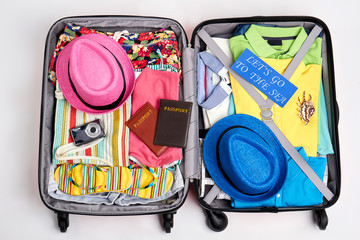Suitcase with beach accessories. Bright clothes for the sea.