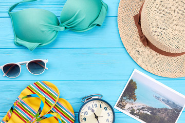 Background from beach accessories. Hat, glasses, bra, slippers, alarm clock, vintage blue background.