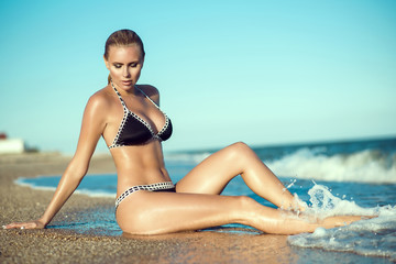 Beautiful suntanned glam blond woman with wet skin and hair sitting on the beach and enjoying, her long legs washed by the sea waves. Resort and spa concept. Copy-space. Outdoor shot