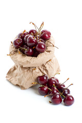Ripe red cherry in a paper bag on a clean white background..