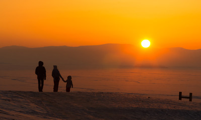 young family with child , holding hands, watching sunset, winter, lake Baikal,Russia.