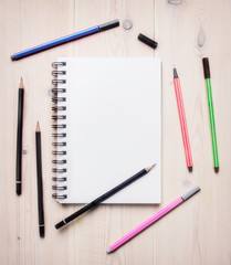 concept of desktop for drawing sketches, notebook with white sheets spread around colored pencils and pens, space for text, border, on a white wooden table