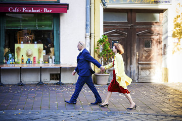 Senior couple walking along street, Munich, Bavaria, Germany