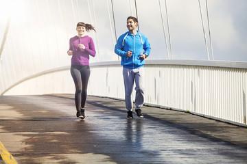 Young couple running on bridge, Osijek, Croatia