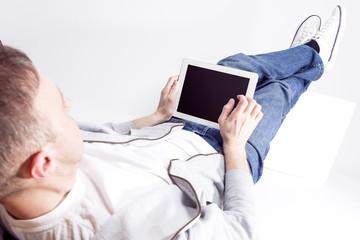 Modern Technology Ideas and Concepts. Portrait of Relaxed Caucasian Man Working with Tablet Computer while Lying on Floor with Legs Lifted on Box in Front.