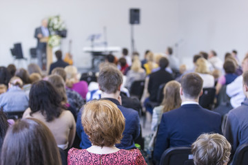 Business Concepts and Ideas. Group of Adults Listening to the Host on Stage During a Conference Indoors.