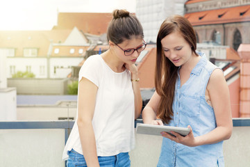 Two young women using digital tablet on balcony, Munich, Bavaria, Germany