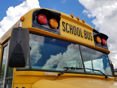yellow school bus with cloud reflection in windshield