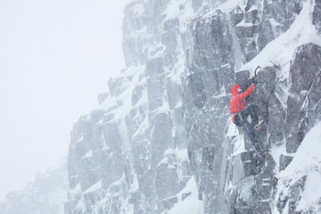 Climber soloing in winter blizzard
