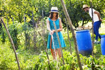 Young woman watering in vegetable garden