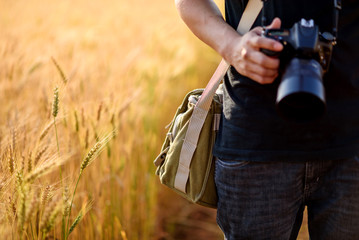 Photographer holding camera on wheat fields in warm sunset