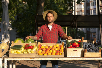 Young man selling fruit and vegetables at market stall
