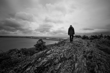 A man stands alone on top of a large bare rock overlooking the sea, black and white