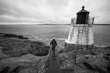 A man walks down path towards Castle Hill Lighthouse in Newport, Rhode Island, on a dreary day, black and white