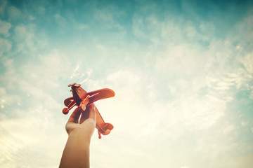 Childhood inspiration - Hands of children holding a toy plane and have dreams wants to be a pilot - Vintage filter effect