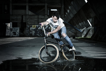 BMX biker performing a stunt on a puddle