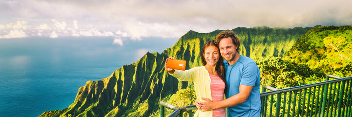 Wall Mural - Travel selfie couple at Napali Kauai Hawaii banner. Young tourists at Na Pali Coast lookout taking mobile phone selfie smartphone photo. Travel people at hawaiian landscape, panorama crop.
