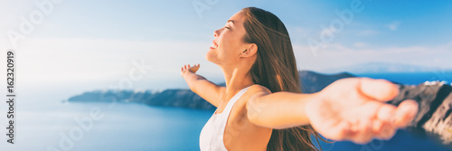 Wall mural Europe cruise Santorini travel free woman banner. Greece vacation carefree freedom with open arms in famous travel holiday. Elegant Asian girl on greek travel luxury resort in Oia Santorini.
