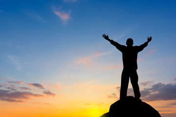 Silhouette of man raised hands at sunset