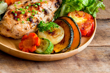 Homemade chicken breast barbecue on wood plate served with grilled vegetables. Delicious chicken barbecue and grilled vegetables for lunch or dinner. Roast chicken breast on rustic wood table.