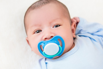 Adorable little newborn baby with pacifier  lying on white bed sheet