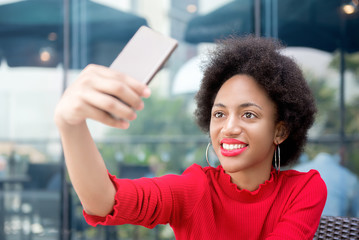 Afro woman taking selfie with smartphone in coffee shop