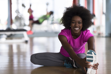 woman in a gym stretching and warming up man in background working with dumbbels