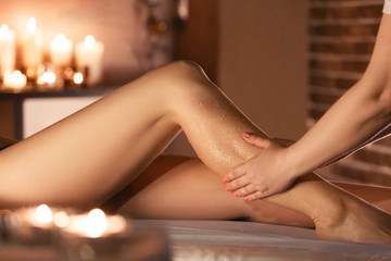 Young woman having feet massage in beauty spa salon, close up